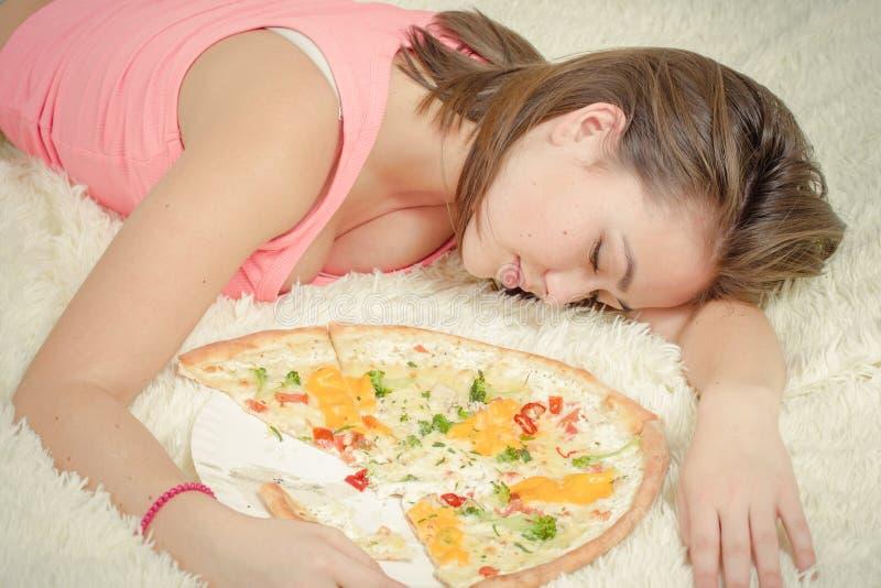 Essen das Mädchenlügen zu viel stockfotografie