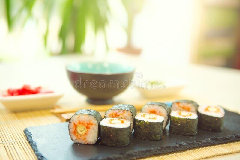Essen der Sushi mit Ess-Stäbchen Sushirollenjapanisches Lebensmittel im Restaurant Kalifornien-Sushirollensatz mit Lachsen, Gemüs lizenzfreie stockfotos