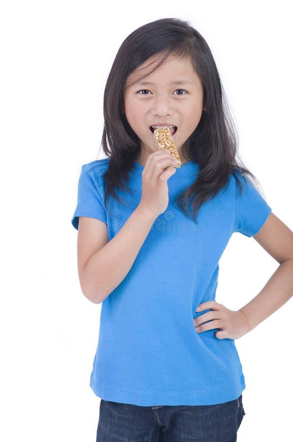 Essen des Granola-Stabes lizenzfreies stockbild