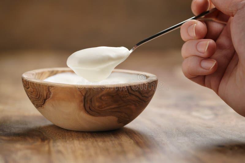 Essen des organischen Joghurts mit Löffel von der hölzernen Schüssel stockbild