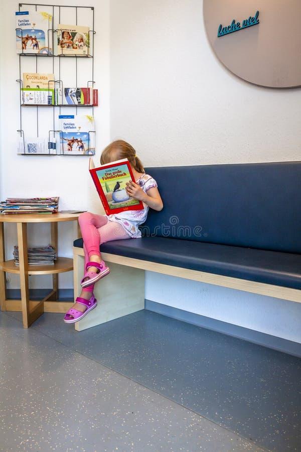 Essen, Duitsland - Juni 11 2018: Meisje geduldig wachten bij Artsenwachtkamer royalty-vrije stock foto