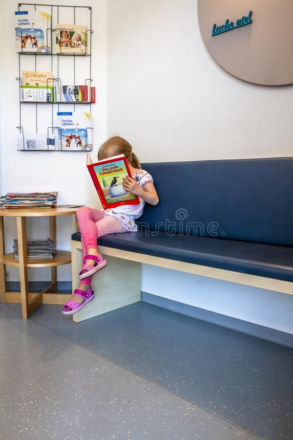 Essen, Germania - 11 giugno 2018: Attesa paziente della bambina ai dottori sala di attesa fotografia stock libera da diritti