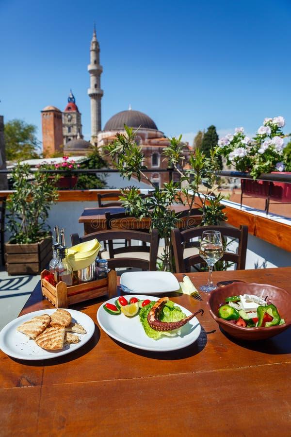 Essen Sie auf dem Tisch gegen Rhodos zu Mittag lizenzfreie stockfotos