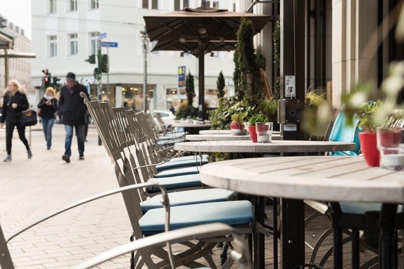 ESSEN TYSKLAND - JANUARI 25, 2017: Illvilja av vintertemperaturer ett kafé erbjuder platser utomhus fotografering för bildbyråer