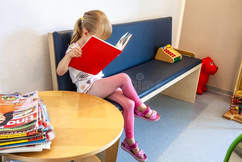 Essen Tyskland - Juni 11 2018: Tålmodigt vänta för liten flicka på doktorer väntande rum royaltyfri bild