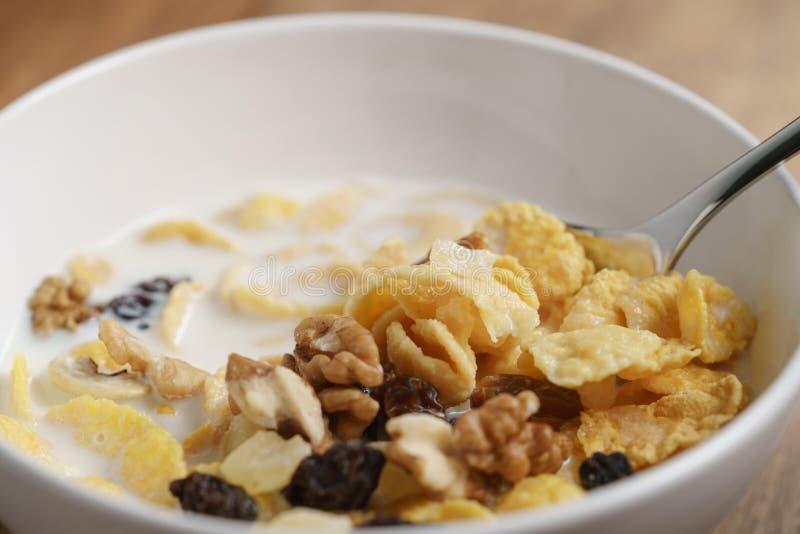 Essen von Corn Flakes mit Früchten und Nüssen in der weißen Schüssel lizenzfreie stockfotografie