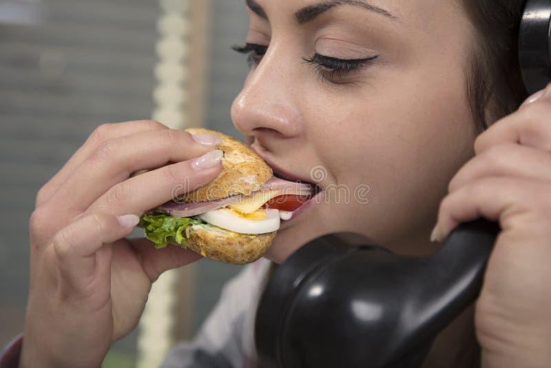 Essen während eines Telefonanrufes stockbild