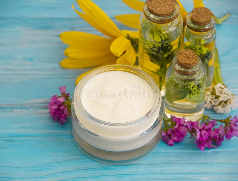 Essence of cosmetic, oil, cream cosmetic herb beauty flowers balm beauty alternative wellness relax on a wooden background stock photography