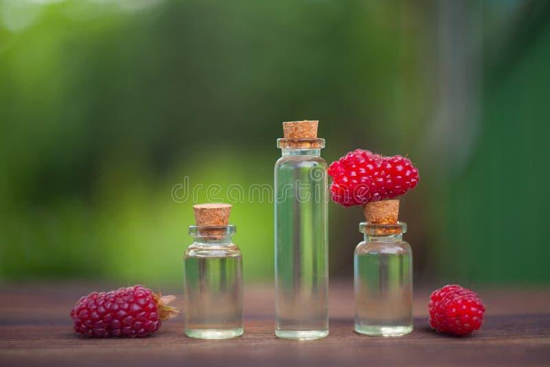 Essence des framboises sauvages sur la table dans la belle bouteille en verre photo stock