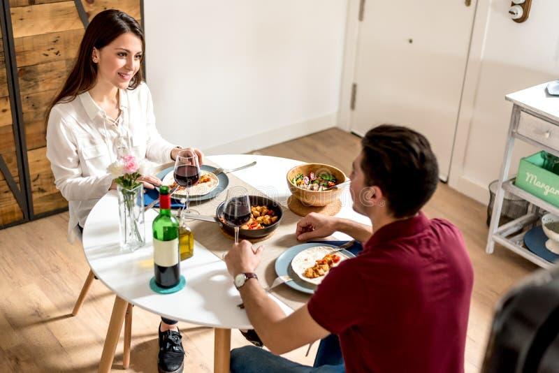Essender und trinkender Wein der glücklichen jungen Paare zu Hause stockfoto