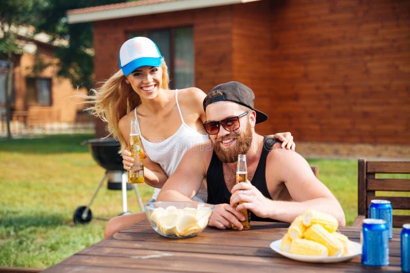 Essendes und trinkendes Bier der netten Paare draußen am Tisch lizenzfreie stockfotos