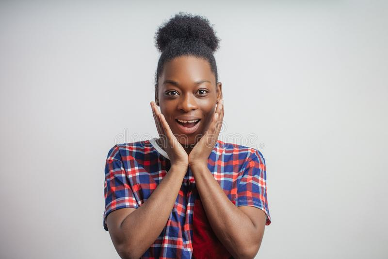 Essendo stupendo con le buone notizie giovane donna di colore emozionale con le mani sulle guance fotografia stock libera da diritti