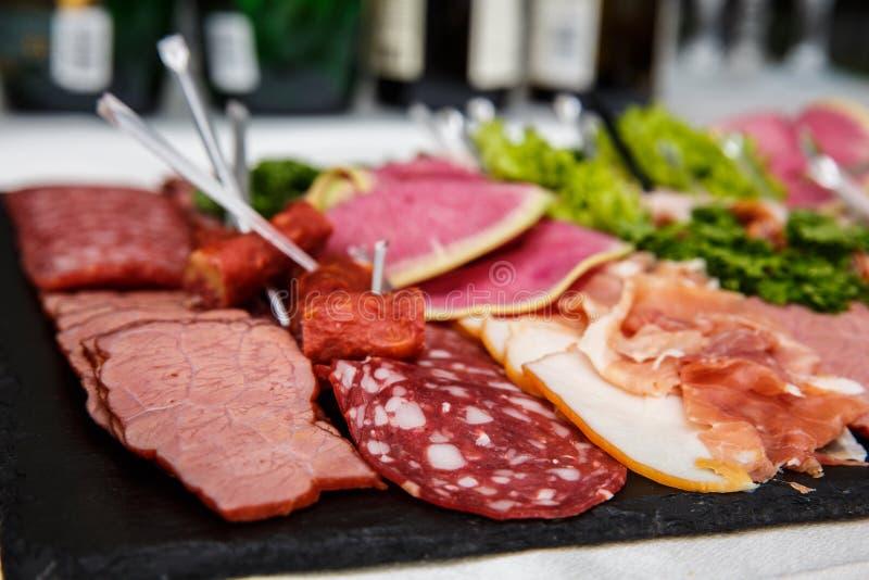 Essenstablett mit köstlicher Salami, Stücke des geschnittenen Schinkens, Wurst, Salat - Fleischservierplatte mit Auswahl stockfoto