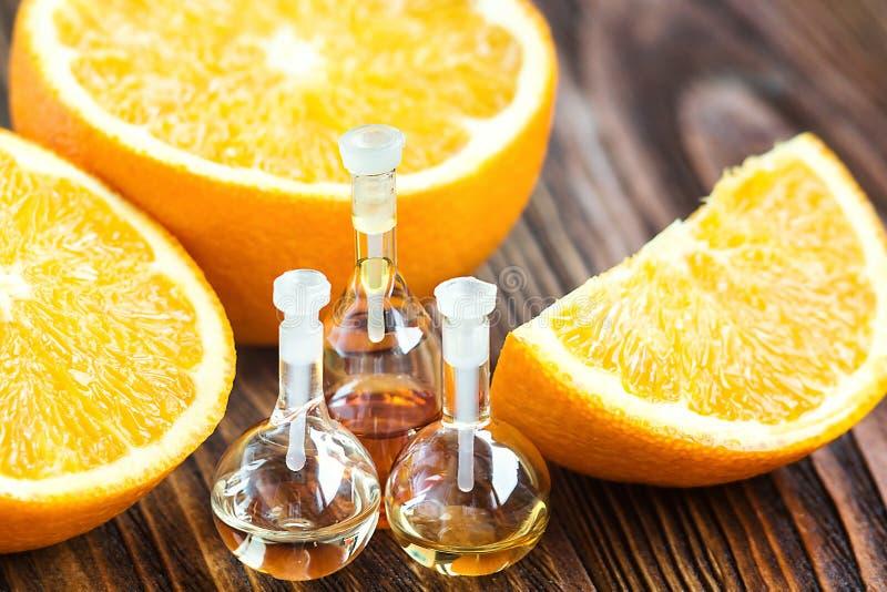 Essentiële aromaolie in glasfles met vers, sappig, rijp, oranje fruit op houten achtergrond De behandeling van de schoonheid Zeep royalty-vrije stock foto's