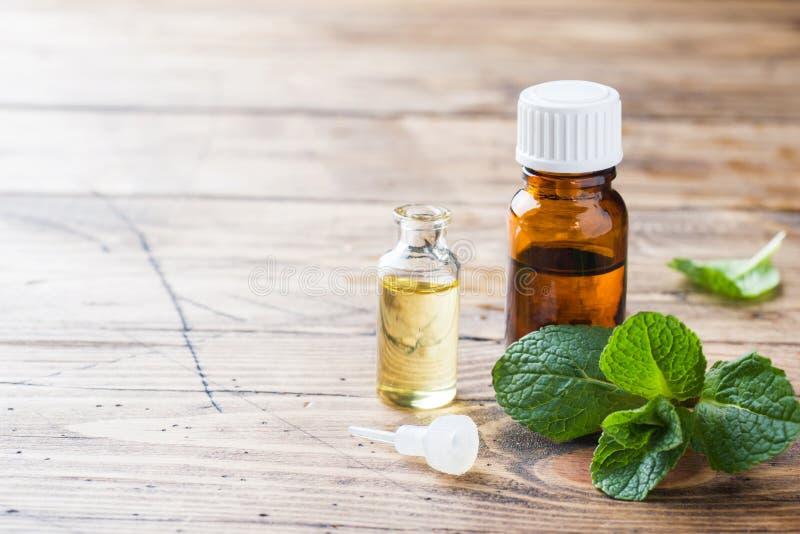 Essentiële aromaolie met pepermunt op houten achtergrond Selectieve nadruk, exemplaarruimte royalty-vrije stock foto's