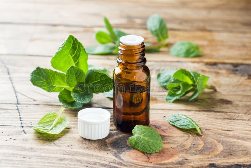 Essentiële aromaolie met pepermunt op houten achtergrond Selectieve nadruk, exemplaarruimte stock foto