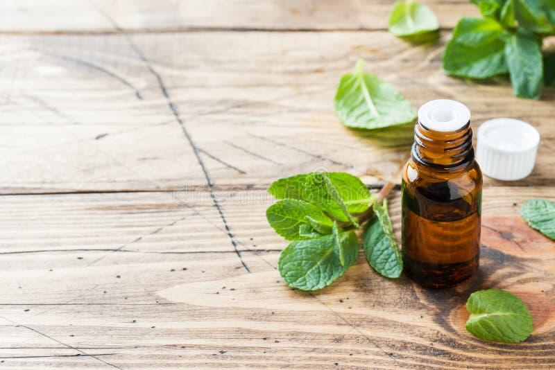 Essentiële aromaolie met pepermunt op houten achtergrond Selectieve nadruk, exemplaarruimte royalty-vrije stock foto