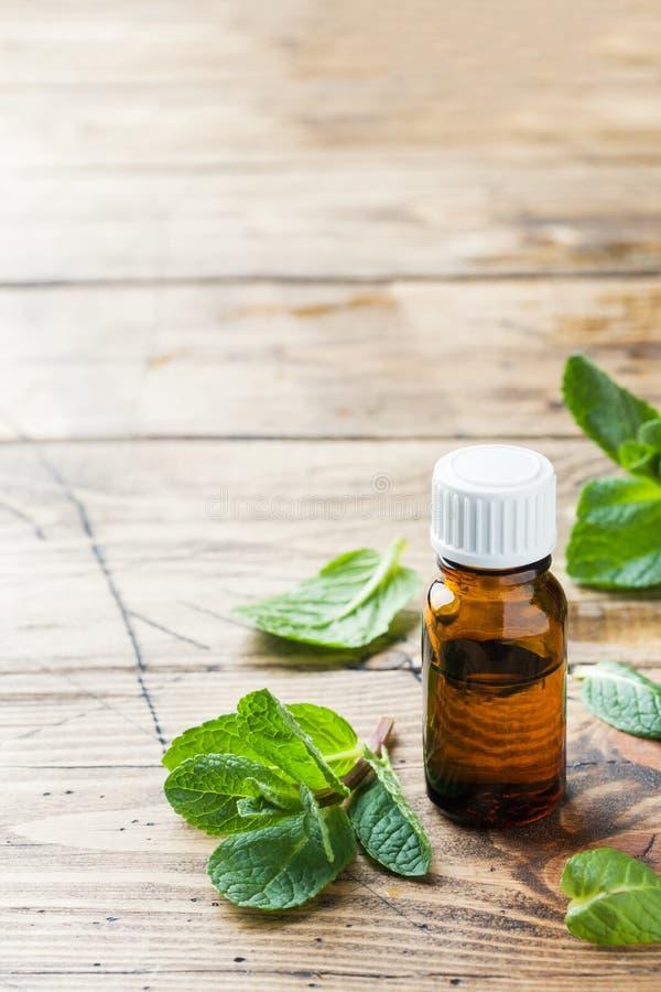 Essentiële aromaolie met pepermunt op houten achtergrond Selectieve nadruk, exemplaarruimte stock afbeelding