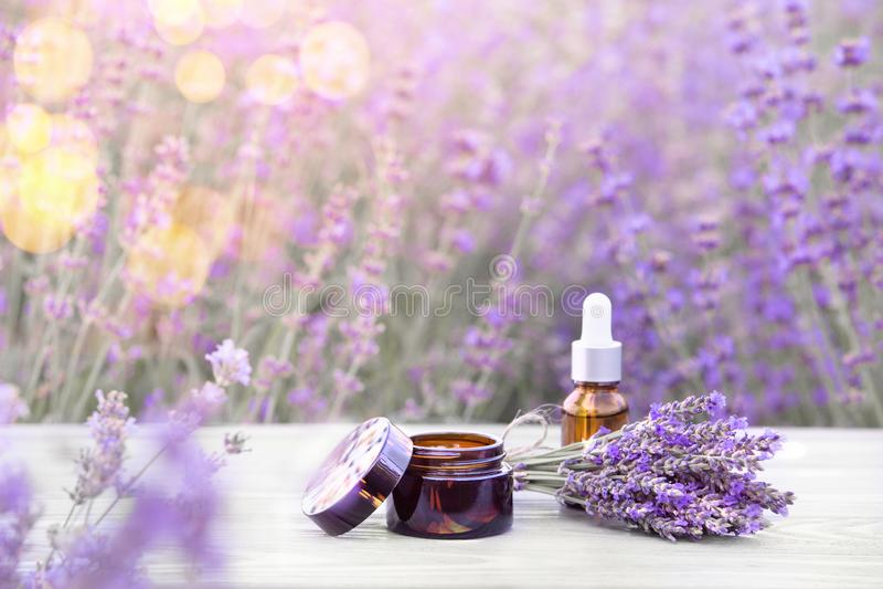 Essentiële lavenderolie in de fles op het grijze houten bureau Horizontale close-up Huidverzorgingscrème stock afbeelding