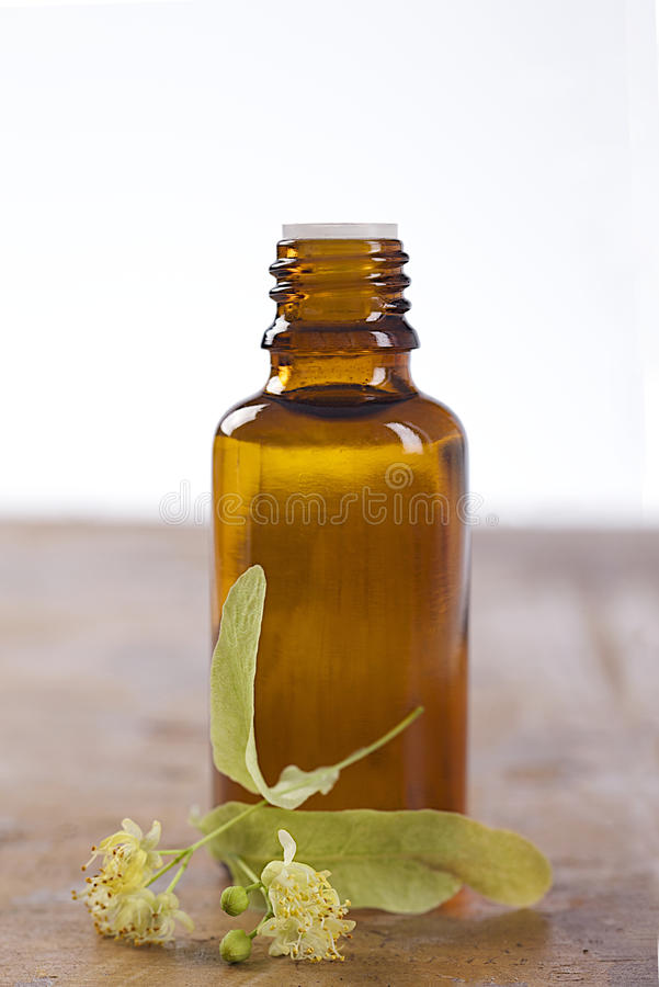 Essential aroma oil bottle with linden on wooden background royalty free stock photo