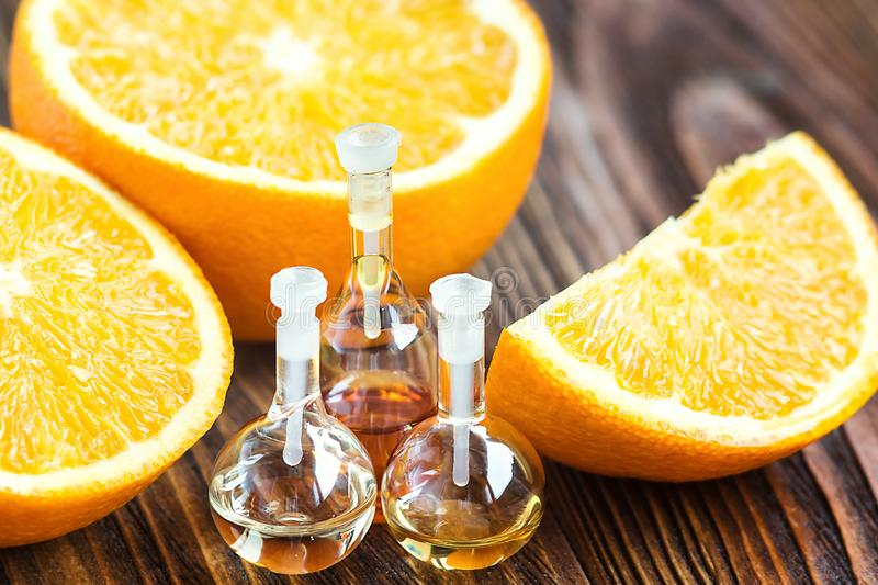 Essential aroma oil in glass bottle with fresh, juicy, ripe, orange fruit on wooden background. Beauty treatment. Spa concept. Sel. Ective focus. Fragrant oil of royalty free stock photos