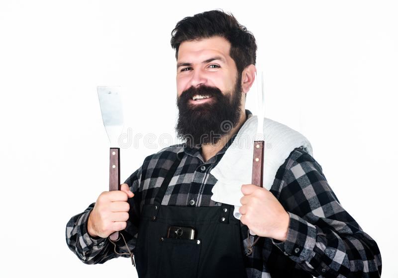 Essential cooking tools. Grill cook using cooking tool set of spatula and grilling fork. Happy hipster holding stainless. Steel cooking utensils. Bearded man stock photography