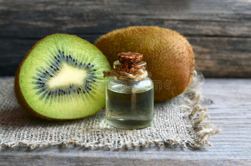 Essential kiwi seed oil in a glass jar with fresh kiwifruit whole and half on old wooden background.Aromatherapy,spa,beauty treatm royalty free stock photo