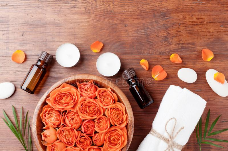Essential oil bottle, rose flower in bowl, towel and candles on wooden table top view. Spa, aromatherapy, wellness, beauty theme. Essential oil bottle, rose stock image