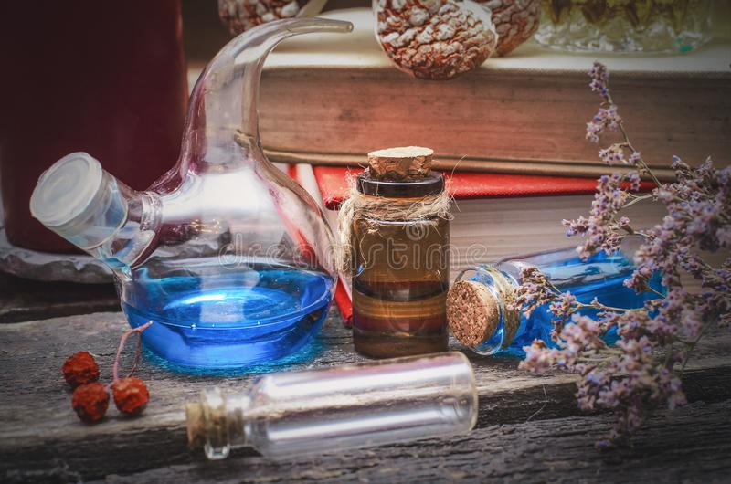 Essential oil bottles. Essential oil bottles and old books. Herbal medicine. Magic potion in the vial on the wizard table. Witchcraft concept stock photos