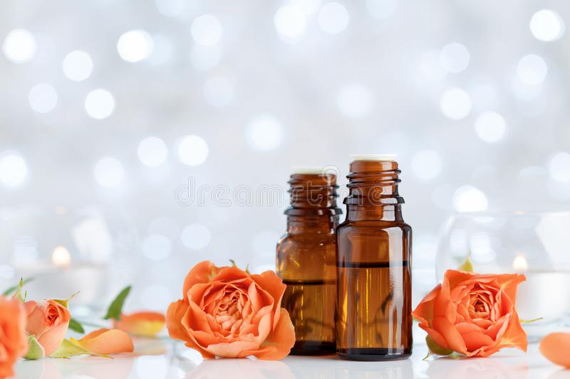 Essential oil bottles with rose flowers on white table with bokeh effect. Spa, aromatherapy, wellness, beauty background. stock image