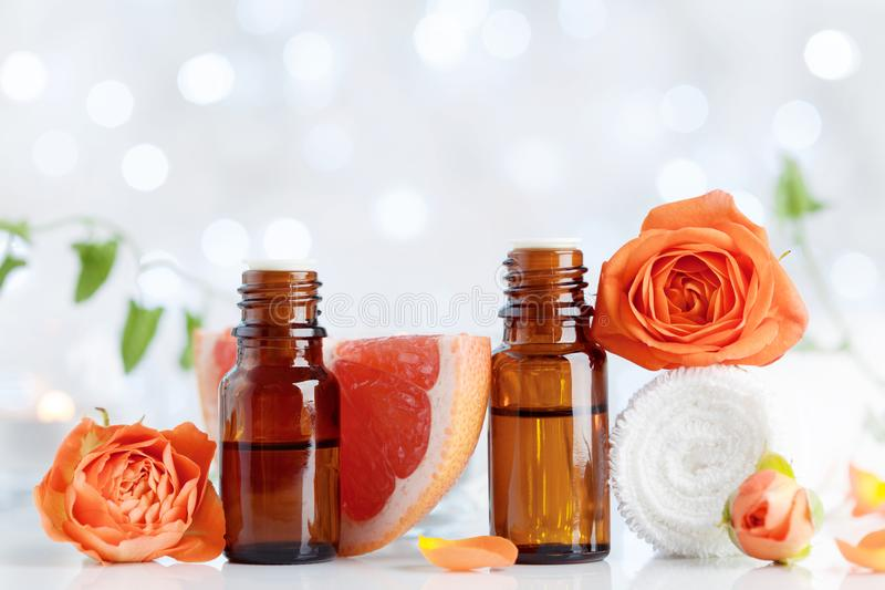 Essential oil bottles with towel, grapefruit and rose flowers on white table. Spa, aromatherapy, wellness, beauty background. stock image