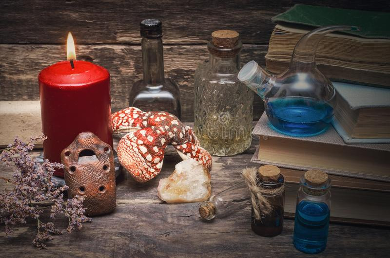 Essential oil on druid table. Magic potion in the vial on the wizard table. Witchcraft concept. Essential oil bottles and old books. Herbal medicine royalty free stock photo