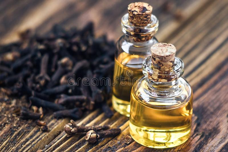 Essential oil in glass bottle and dry cloves on dark wooden background copy space beauty treatment. Fragrant oil of cloves, macro,. Image. Spa concept royalty free stock photography