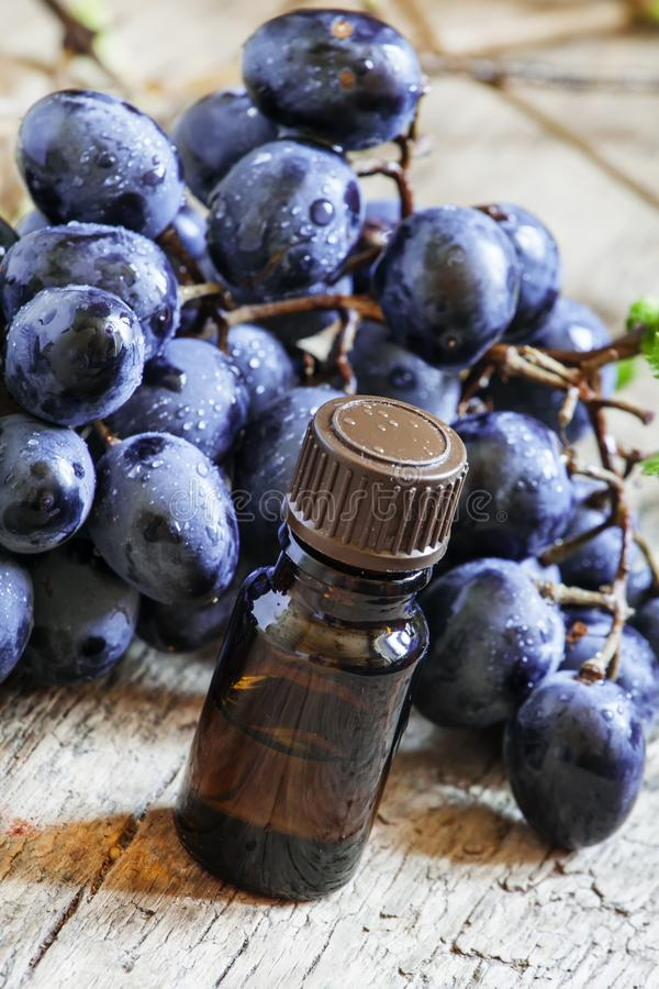Essential oil of grape, vine, blue grapes, old wooden background stock photos