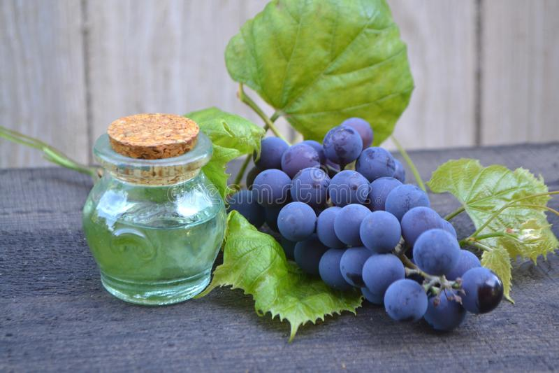 Essential oil of grape, vine, blue grapes, old wooden background in russian style stock images
