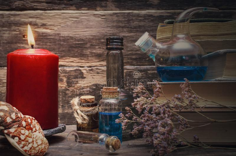 Essential oil. Herbal medicine. Essential oil bottles and old books. Herbal medicine. Magic potion in the vial on the wizard table. Witchcraft concept royalty free stock photo