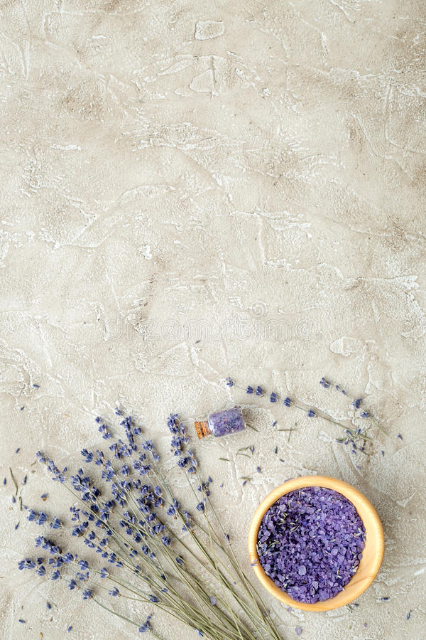 Essential oil and lavender salt with flowers top view. Gray background stock photography