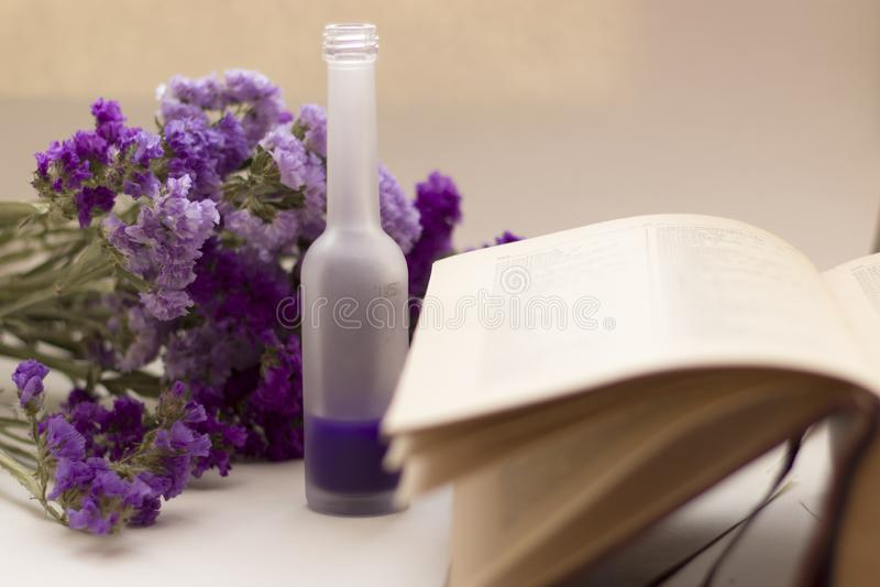 Essential oil in matt bottle on purple flowers blur background. Essential oil in matt bottle on purple flowers blur background stock images