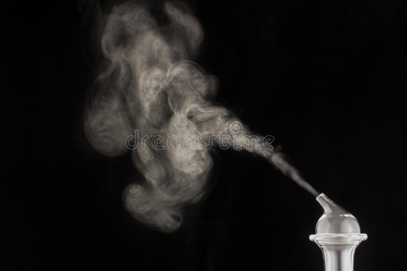 Essential Oil Nebulizer. Vapor, smoke, or essential oil emitting from a glass nebulizer on a black background stock photo