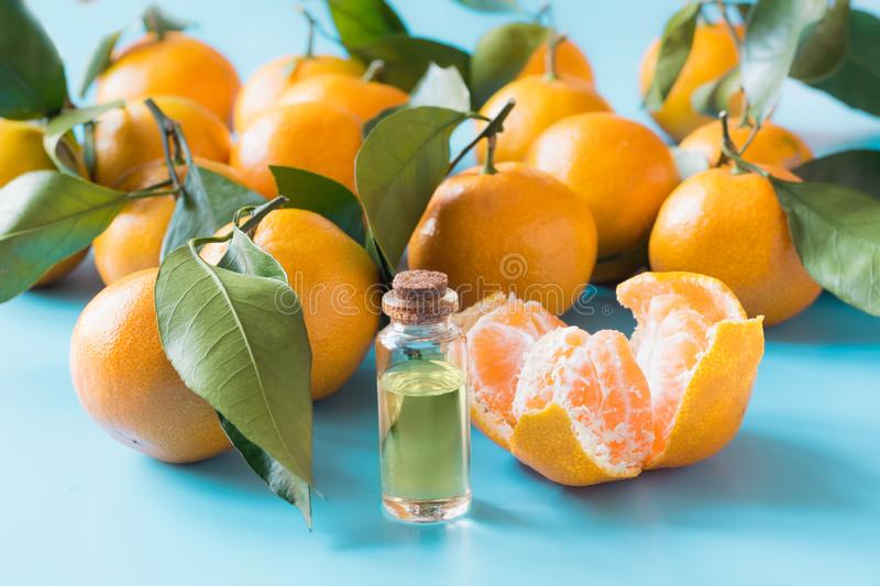 Essential oil of orange mandarin in glass bottle over pastel blue background. Skincare concept royalty free stock photos