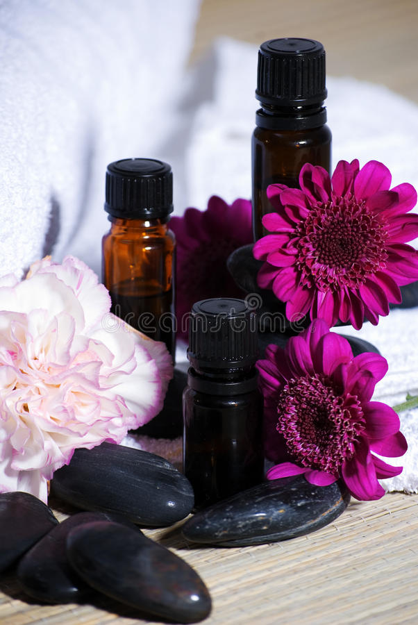 Essential oils and flowers. A vertical image of essential oils and flowers in a spa setting royalty free stock images