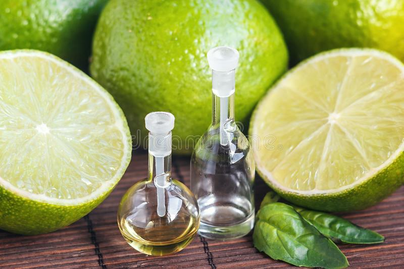 Essential oils in glass bottle with fresh, juicy, ripe limes. Beauty treatment. Spa concept. Selective focus. Small bottles of per stock photography
