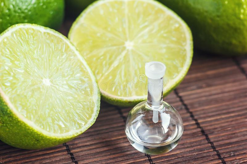 Essential oils in glass bottle with fresh, juicy, ripe limes. Beauty treatment. Spa concept. Selective focus. Small bottles of per stock images