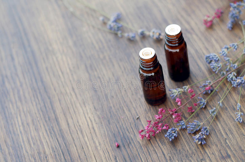 Essential oils and herbs on wooden background stock photo