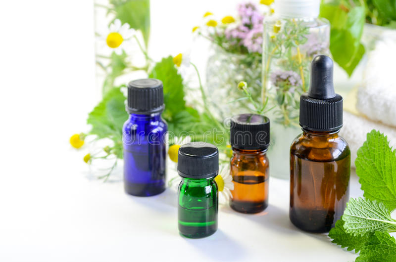 Essential oils and natural cosmetics with herbs. Essential oils and natural cosmetics with herbal leaves and flowers royalty free stock images