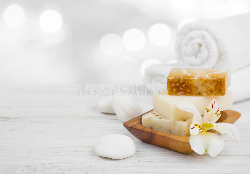 Essential spa products on wooden surface over abstract lights background royalty free stock images