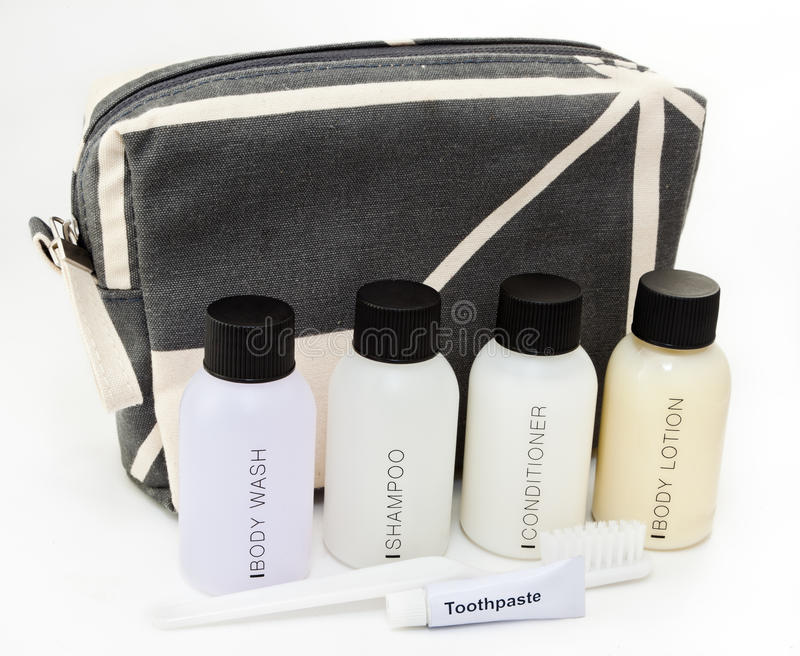 Essential travel toiletries. Travel toiletries kit in front of a small toiletries bag royalty free stock photos