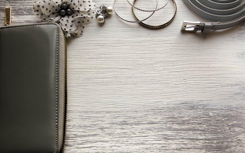 Essentials fashion woman objects. Female accessories: wallet bracelets earrings belt royalty free stock photography