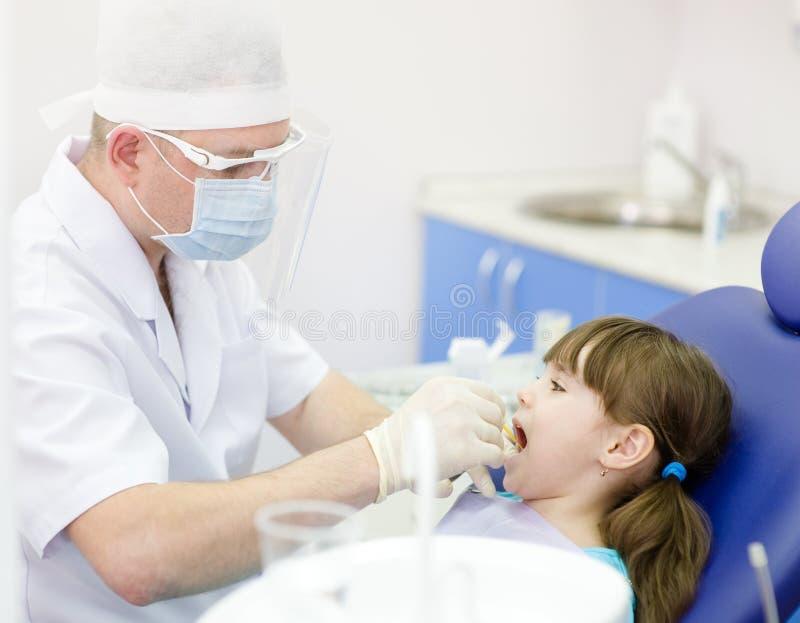 Essere dato d'esame dentario alla ragazza dal dentista immagini stock libere da diritti