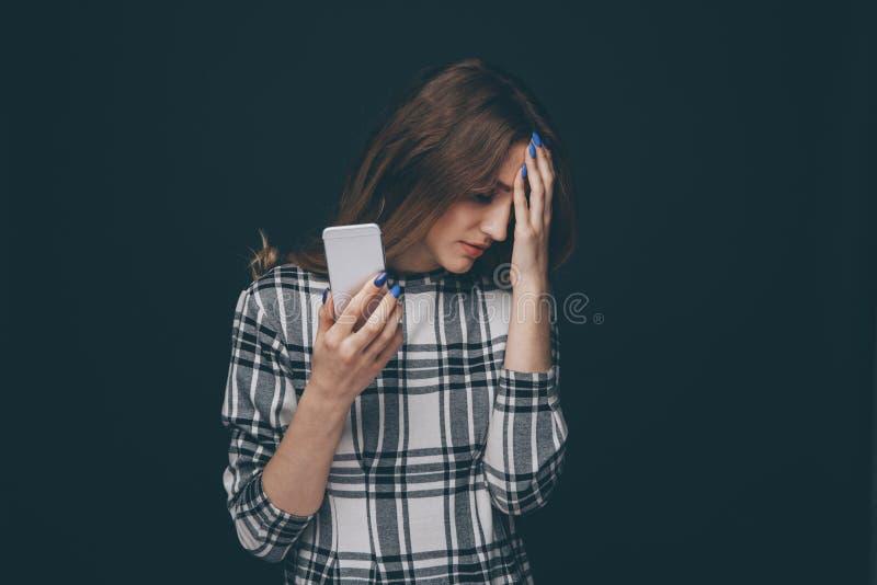 Essere teenager triste vittima del cyberbullismo online che si siede su uno strato nel salone a immagine stock